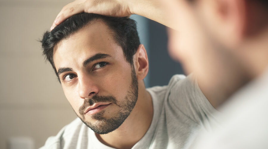 man looking at styled hair in mirror