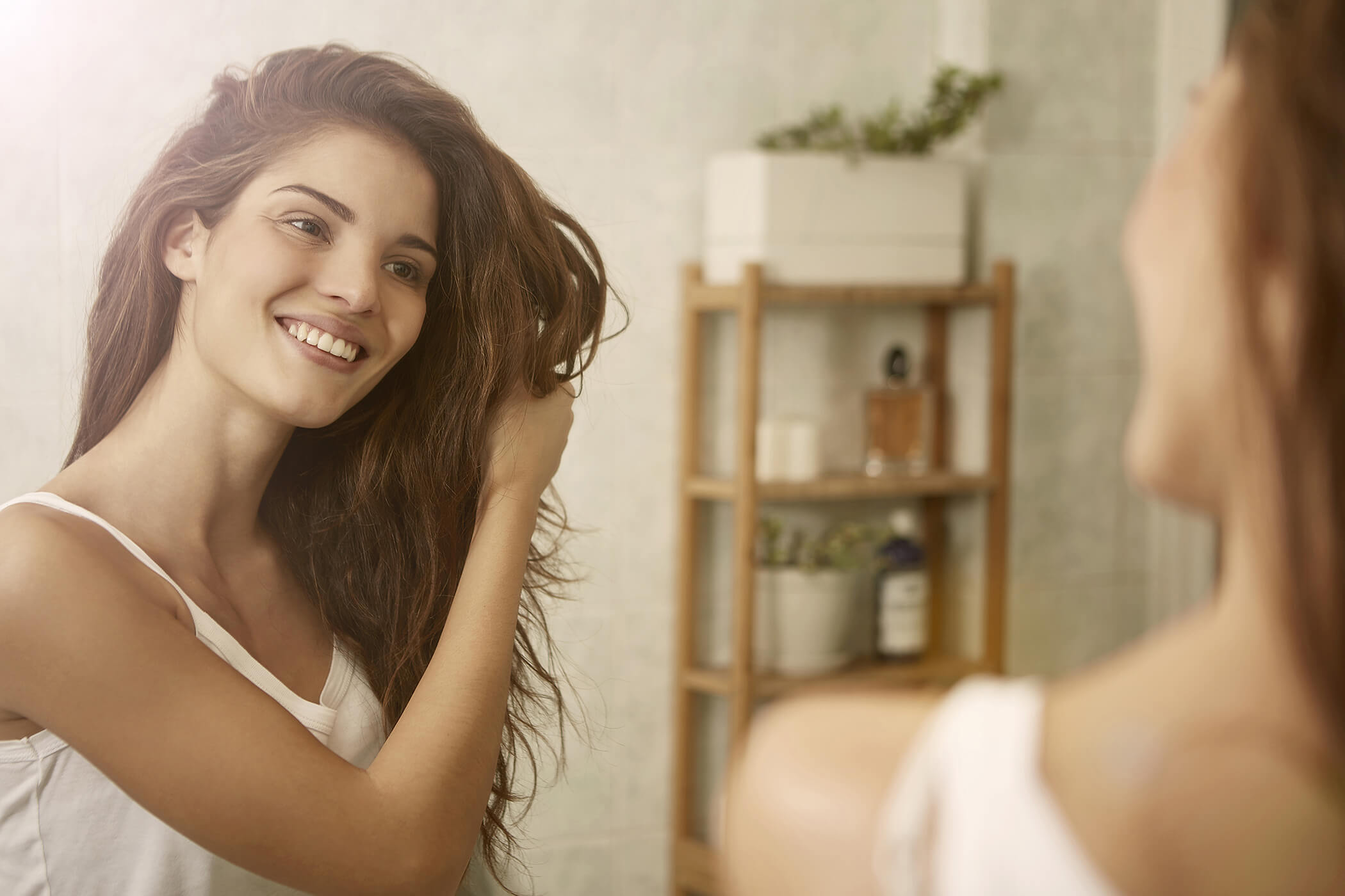 girl doing hair in mirror