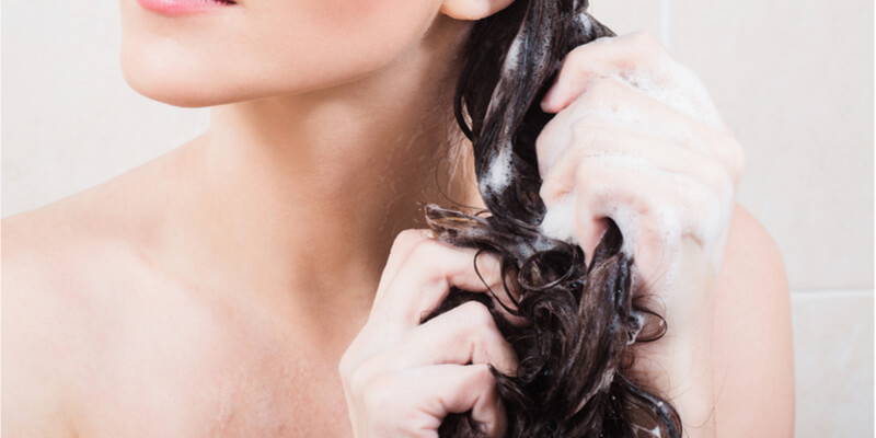 lady putting conditioner on her hair