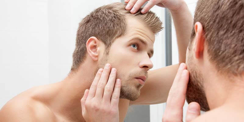 male checking hair loss